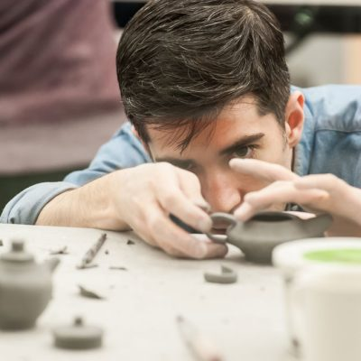 Man working on clay teapot