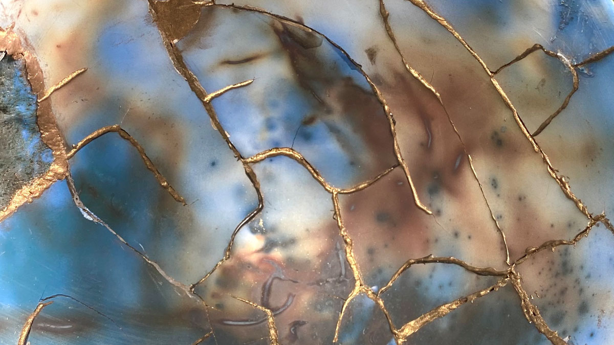 Close up of a ceramic bowl with kintsugi-inspired gold mending