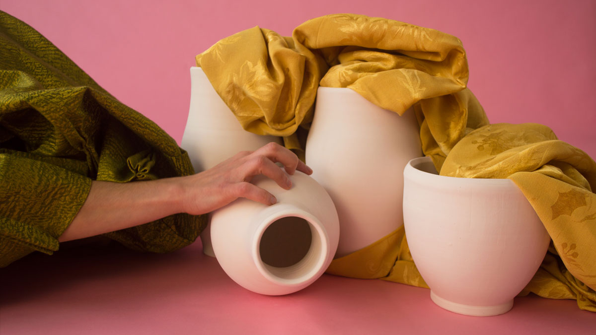 A hand grasping a white ceramic vessel and draped fabric