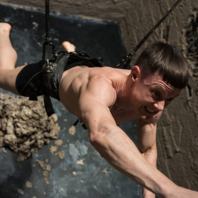 Artist Cassils in a harness reaching up with a pile of clay beneath them