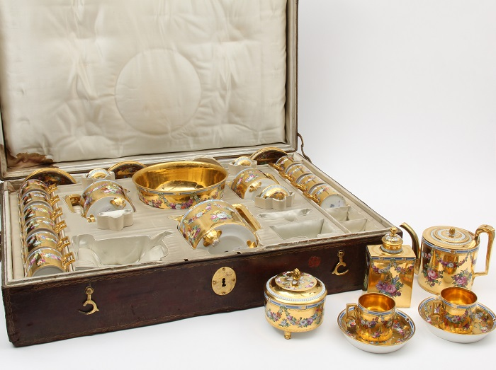 Golden chocolate service, featuring cups, saucers, and pouring vessels, inside a leather case