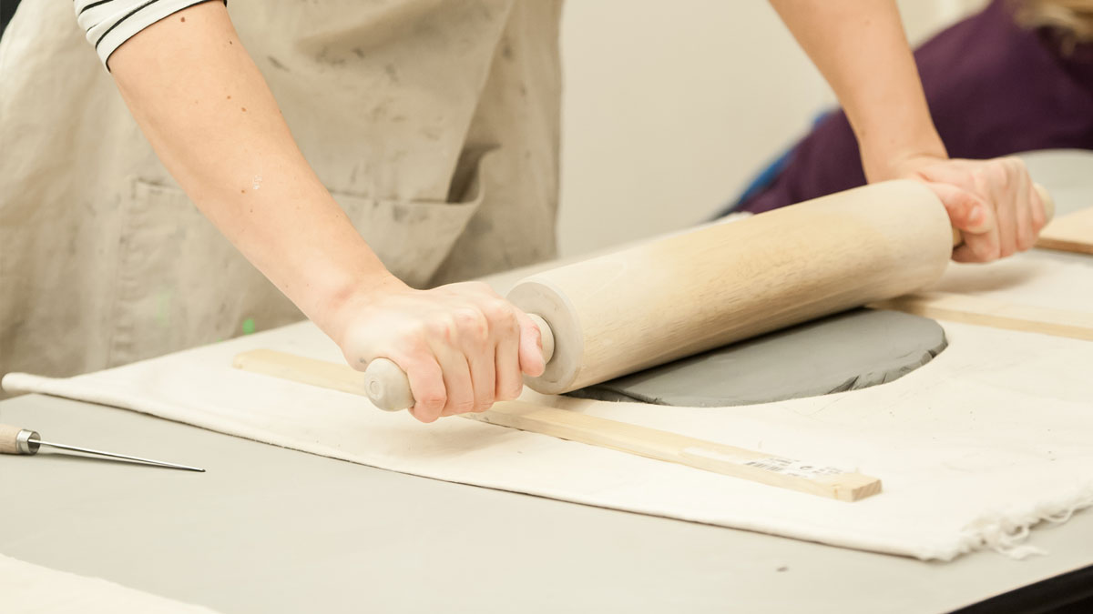 Person rolling out a slab of clay