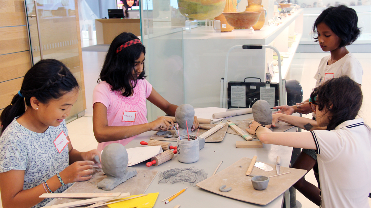 Four children working with clay in a pottery studio