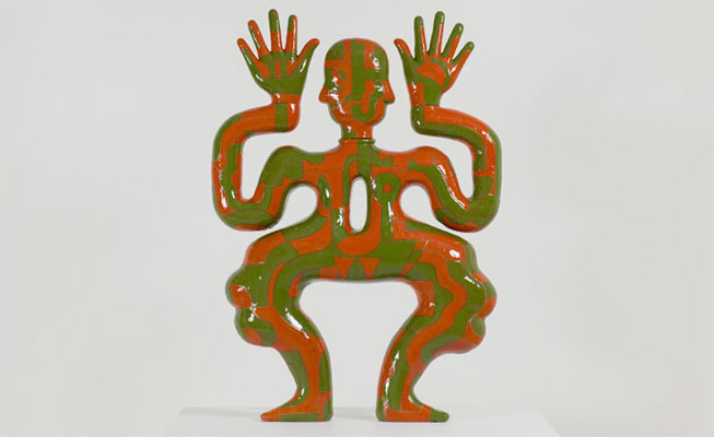 Green and red ceramic figure with wavy limbs