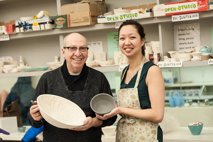 Two people holding clay bowls made on the pottery wheel