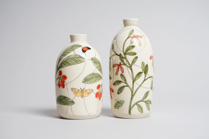 Two ceramic vases decorated with plants and insects