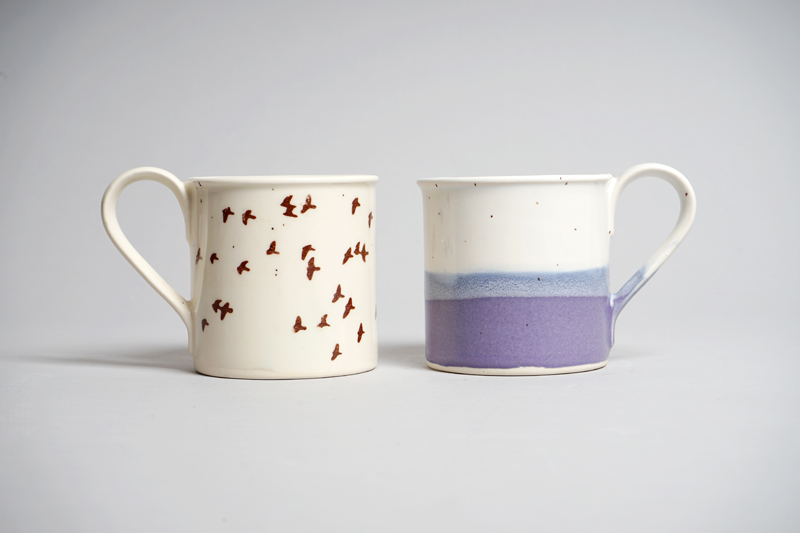 Two white ceramic mugs with decoration