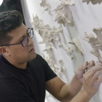 Artist David Salazar installing his ceramic birds