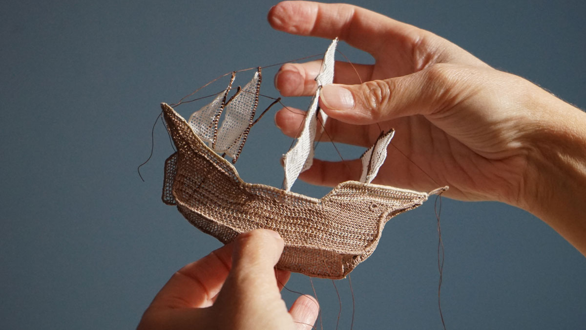 Artist Dorie Millerson holding a ship made from needle lace, cotton, and wire