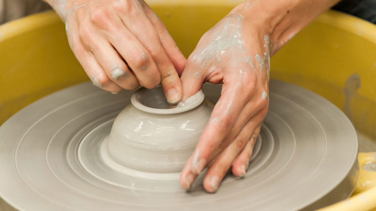 Hands making a vessel on the potter's wheel