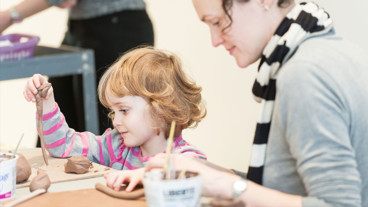 Mother and daughter at a table making ceramics