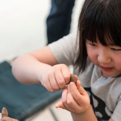 Child shaping a clay object
