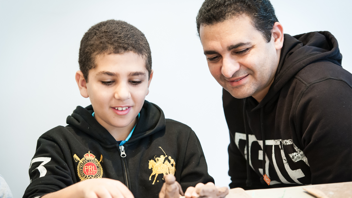 A boy and his father sculpting objects with clay
