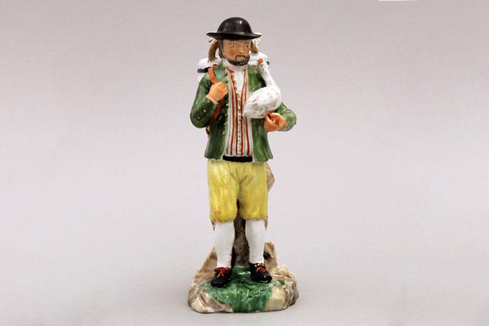 Porcelain figure of a farmer holding a goose