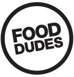 """Black circle with black writing reading """"Food Dudes"""" in the centre (Food Dudes logo)"""