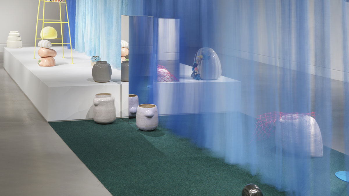 Installation of ceramics vessels with a large blue curtain