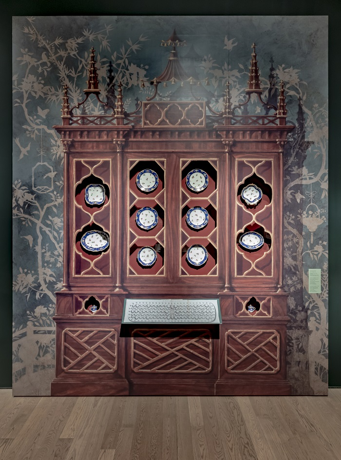 A painted wooden cabinet with real ceramic plates inserted in cutouts