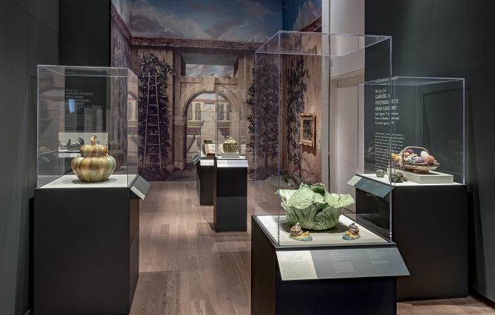 Savour: Food Culture in the Age of Enlightenment. A painted garden archway is in the background. Cases filled with ceramic objects including a cabbage, pumpkin, as well as knitted vegetables are in the foreground