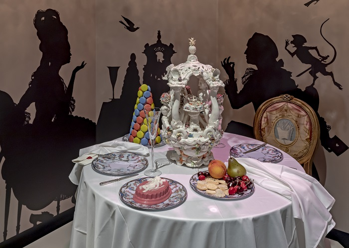 A dining table with plates of realistic ceramic and plastic food, and a painted backdrop of a romantic dining scene is in the background