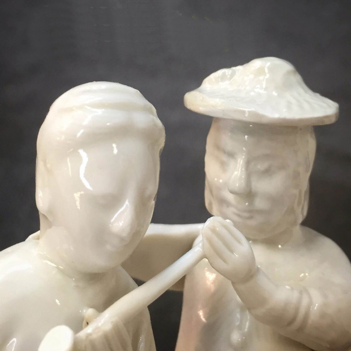 Two white ceramic figures, one with a pipe