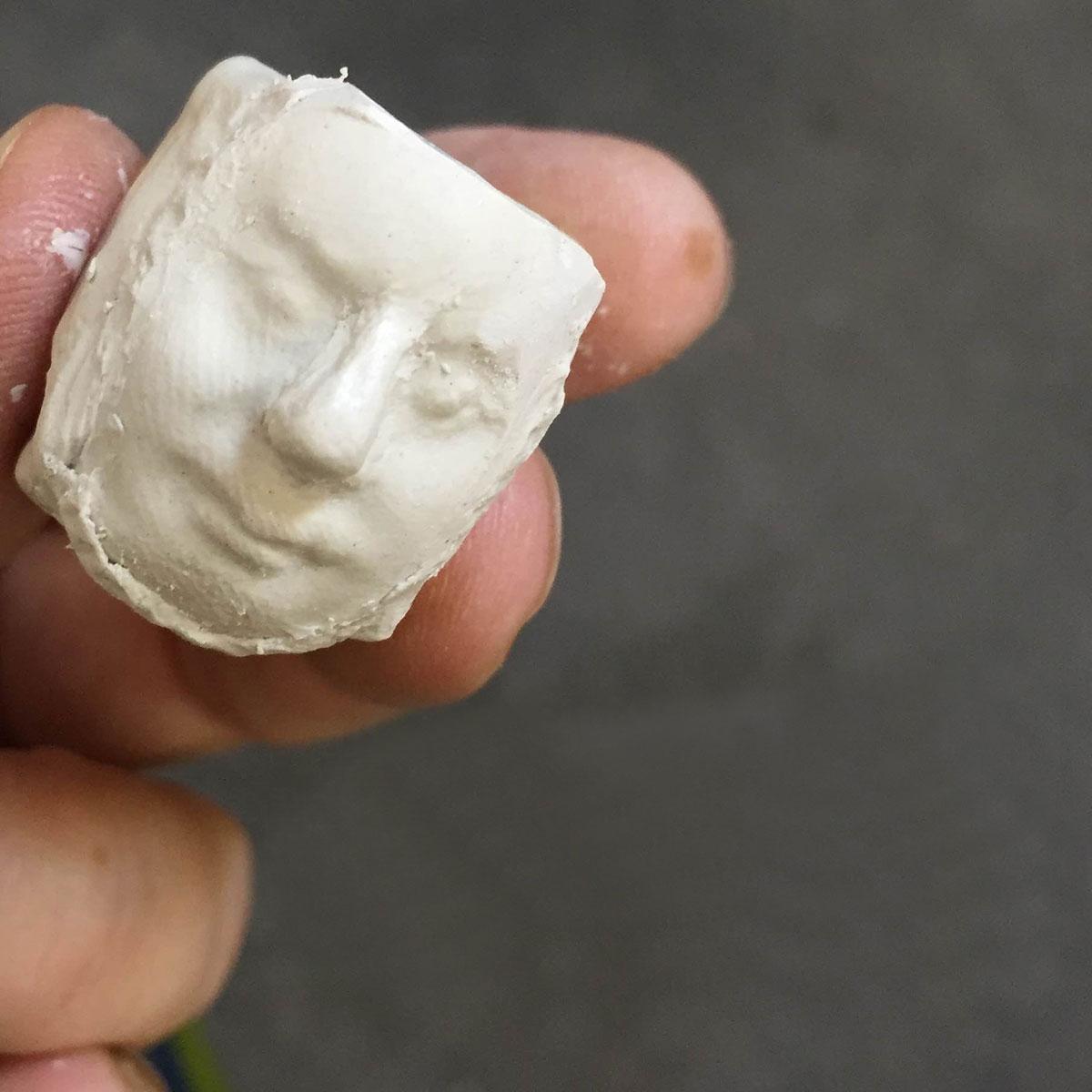 Hand holding clay head