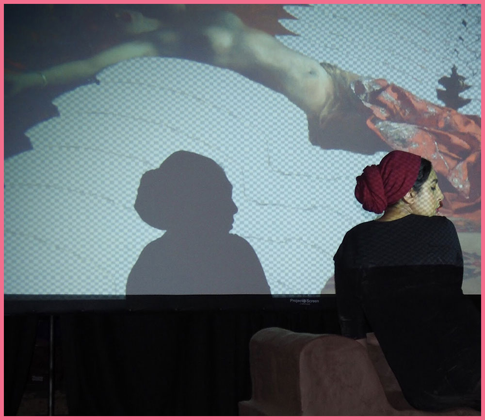 Artist Habiba El-Sayed in profile in front of a screen