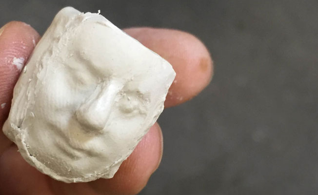 Hand holding white clay head