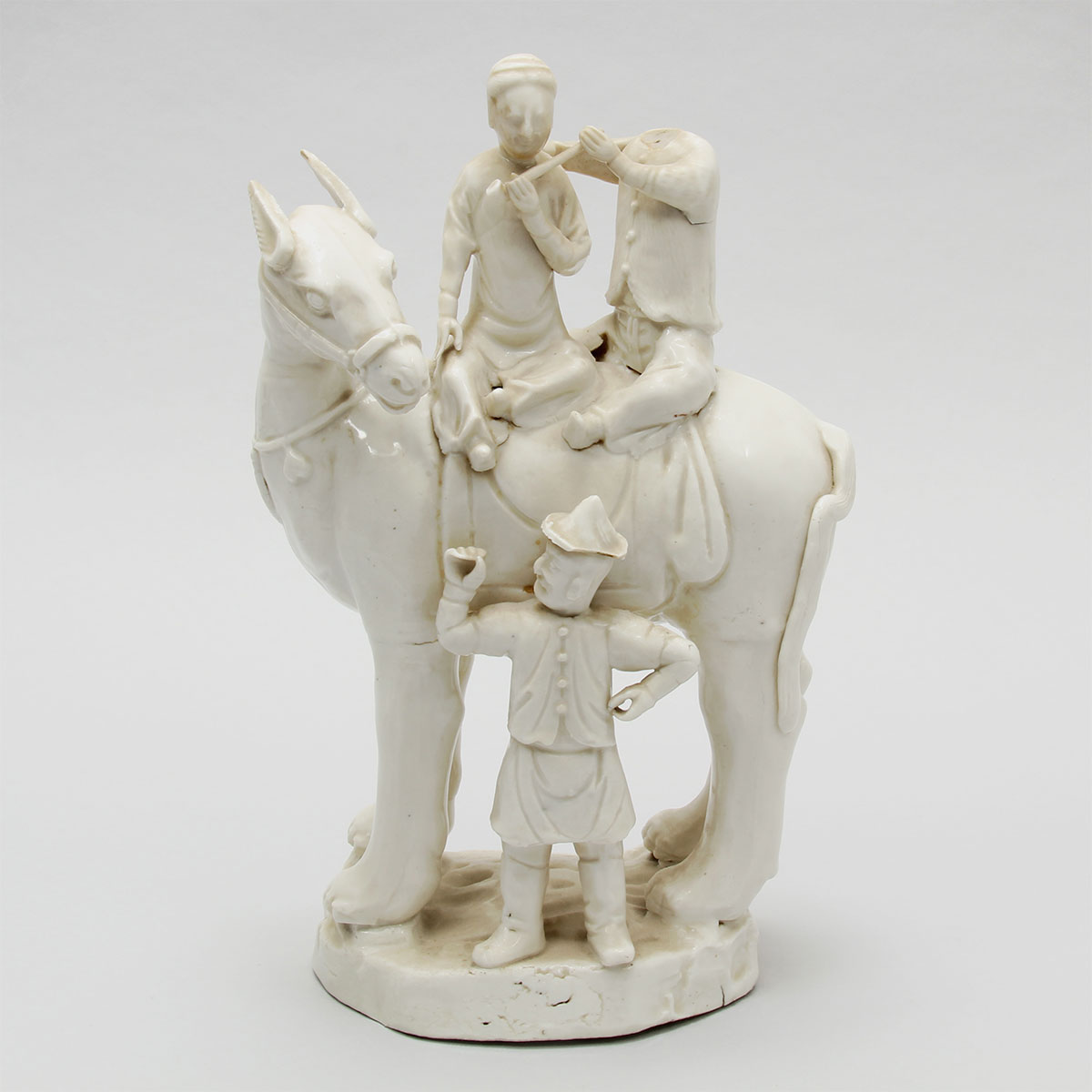 White porcelain figure of a horse and three men
