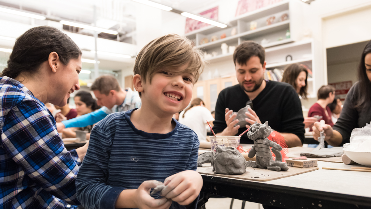 Child holiday clay smiling in the foreground with people working with clay in the background