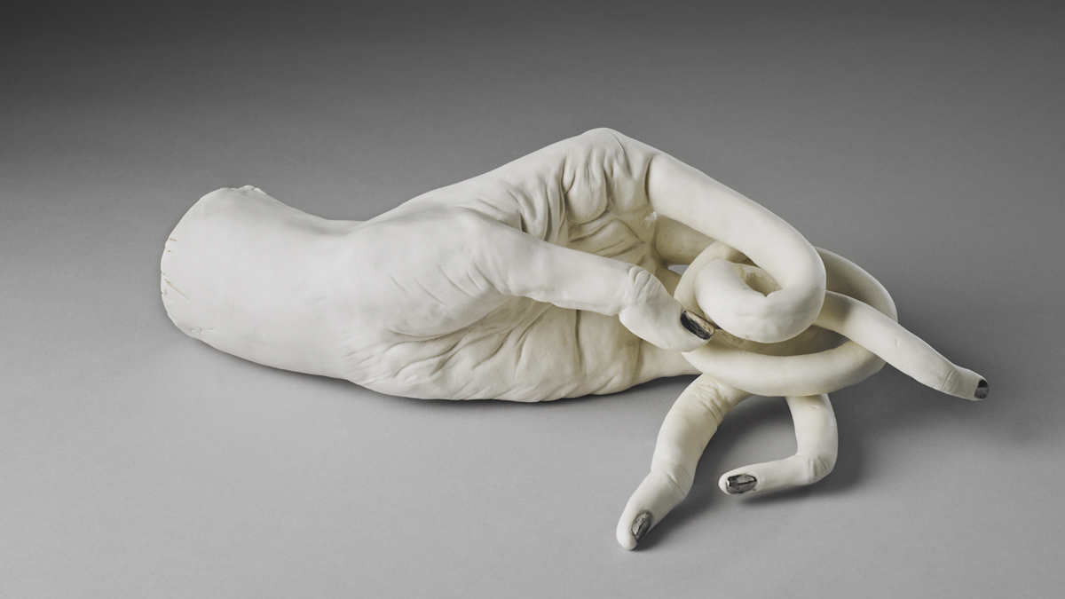 White ceramic hand with twisted fingers and silver painted nails by Shary Boyle