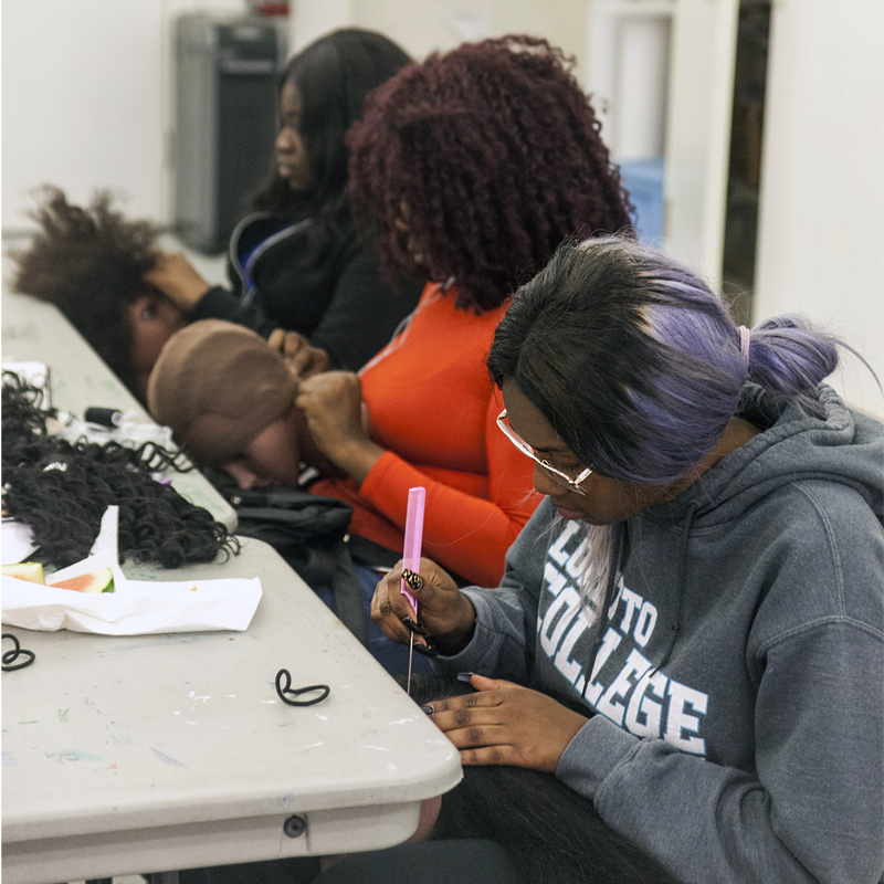Three young women working on wigs