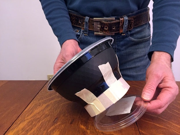 Taping a plastic lid underneath a take out container