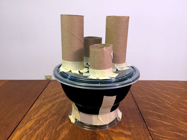 Toilet paper rolls of various heights taped to a take out container