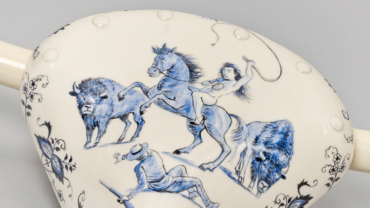 Detail of a ceramic bicycle seat by Kent Monkman showing Miss Chief on a horse about to whip a Mountie