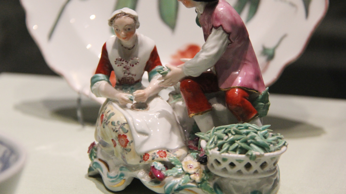 Two porcelain figures shelling peas