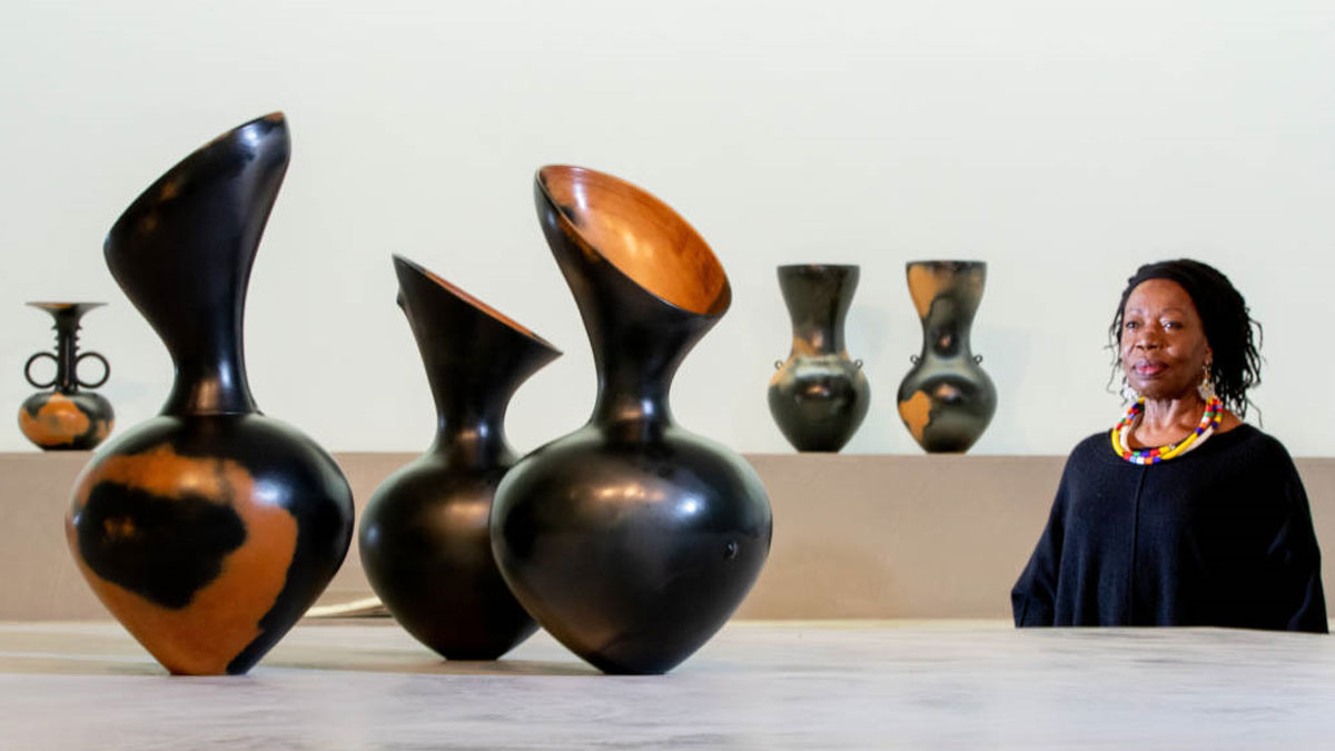 Artist Magdalene Odundo with her ceramic vessels