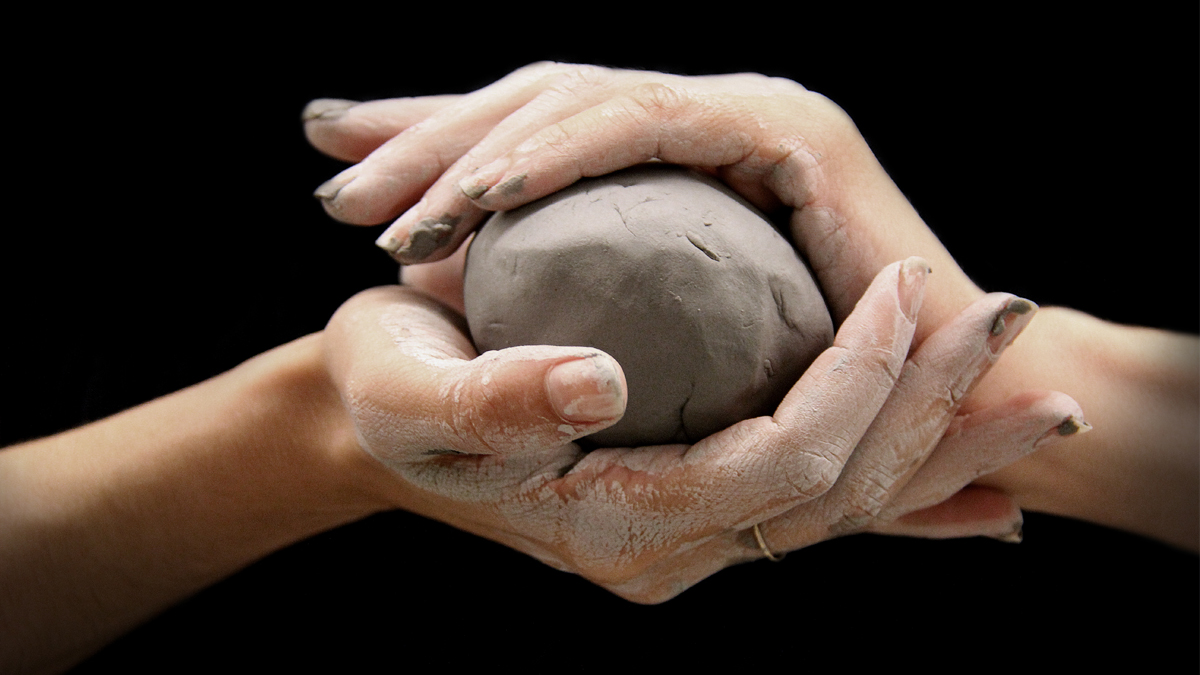 Hands wrapped around a ball of clay