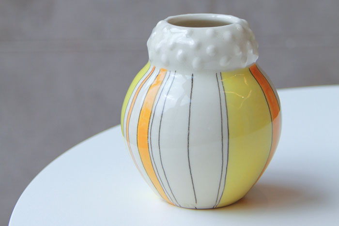 Small white ceramic vase with orange and yellow stripes
