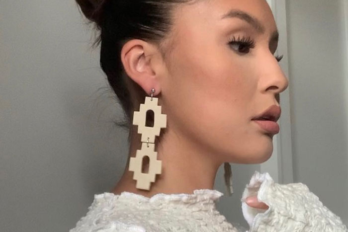 Woman wearing a pair of nude ceramicsearrings made of geometric shapes