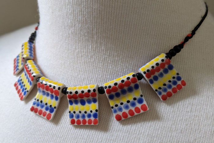 Necklace with square ceramic beads dotted with blue, red, and yellow glaze