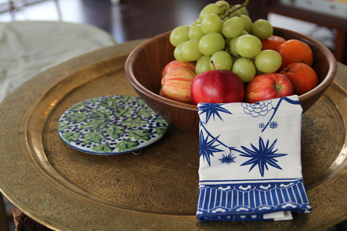 Blue and white tea towel draped over a wood bowl filled with fruit