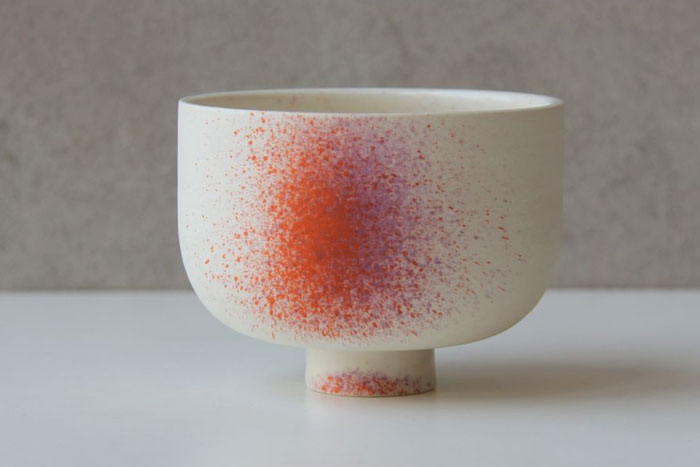 White ceramic cup with orange and purple spatter paint