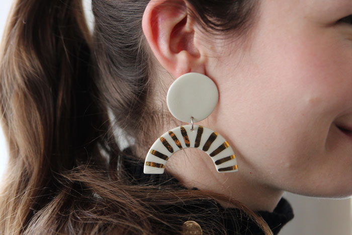 Woman wearing white ceramic earrings while a circular stud and dangling half moon with gold stripes