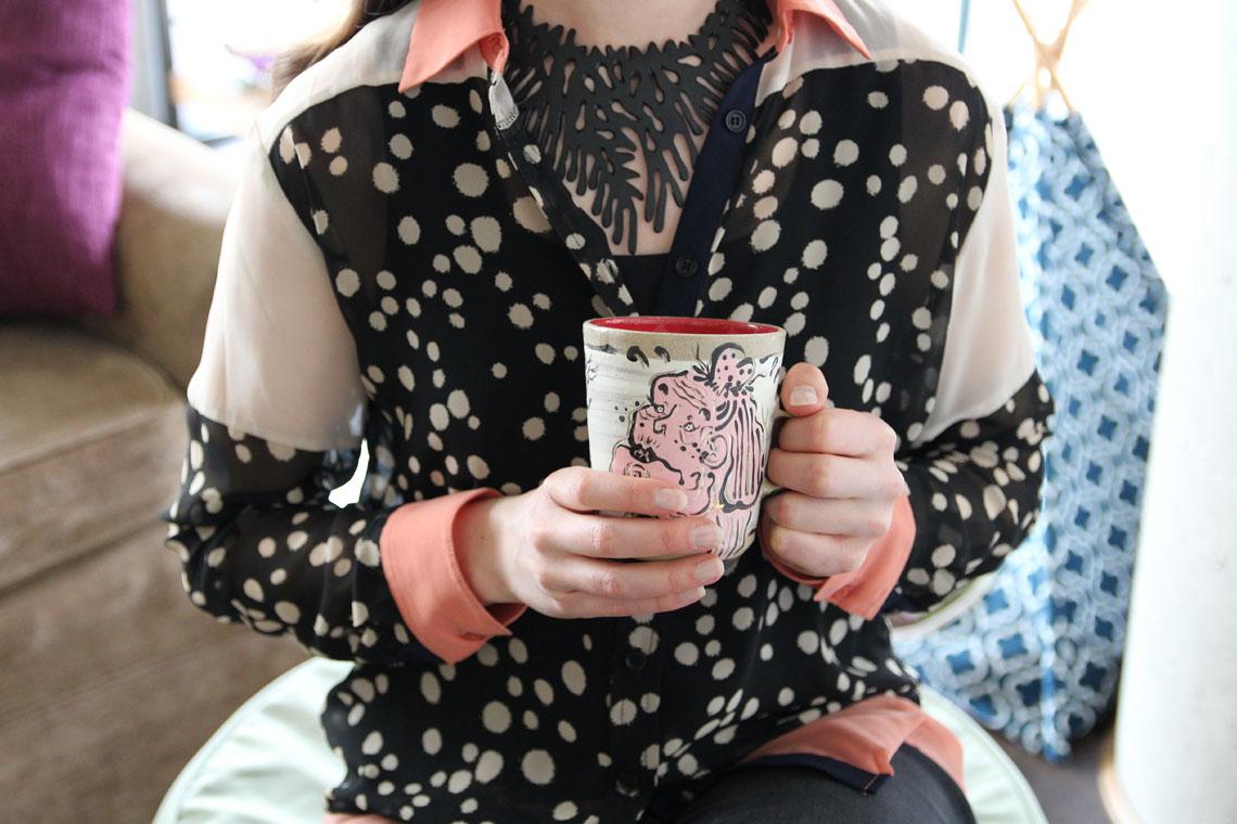 Woman wearing a polka dot shirt holding a mug