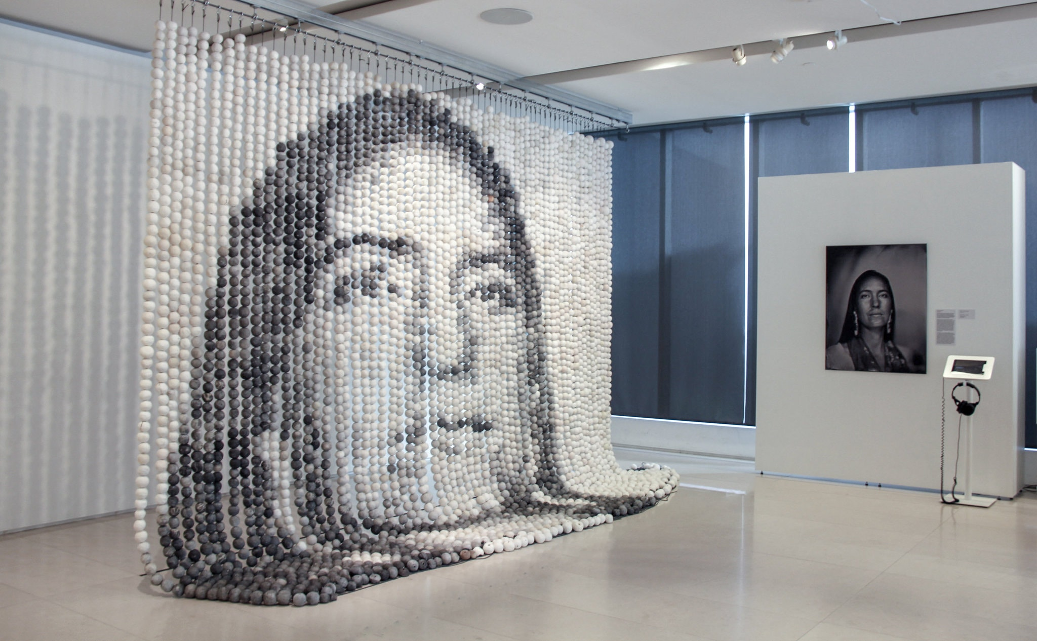 Ceramic bead curtain forming an image of a woman's face, next to the original photo of the woman