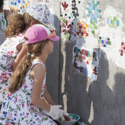 Two girls putting colourful tiles on a concrete wall
