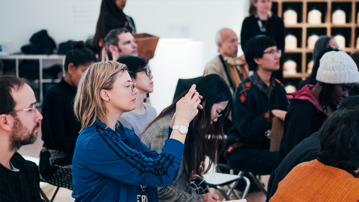 A group of people taking part in an in-gallery workshop with a woman in the centre taking a photo with her phone