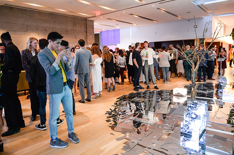 Crowd of guests at SMASH 2018 with a guest taking a picture on his phone of an installation made up of broken mirror shards