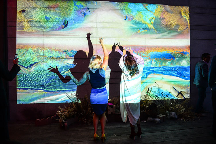 Two party guests in front of a digital landscape installation with their backs to the camera
