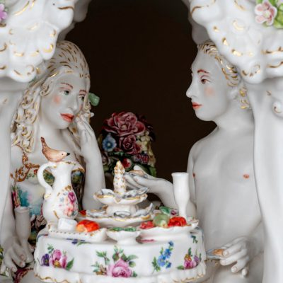 Image of two white porcelain figurines at a dining table surrounded by flowers